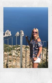 Heidi Brewer smiling with sunglasses on, blue floral shirt, and white shorts holding wire gate with ocean in background