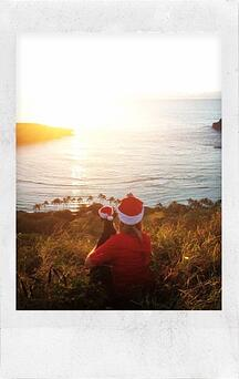 Heidi Brewer in santa hat with arm around dog wearing a santa hat back to camera watching a sunset over the water