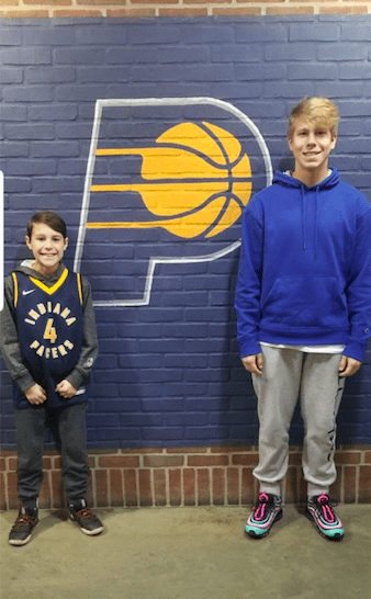 Tim Sanabria's sons standing in front of Indianapolis Pacer's logo painted on brick wall